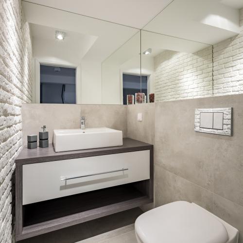 småt badeværelse med mursten på væggen